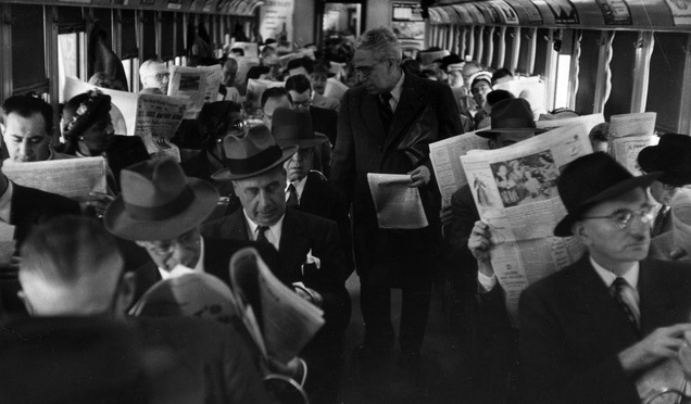 Commuters reading newspapers on a train in Philadelphia, circa 1955.